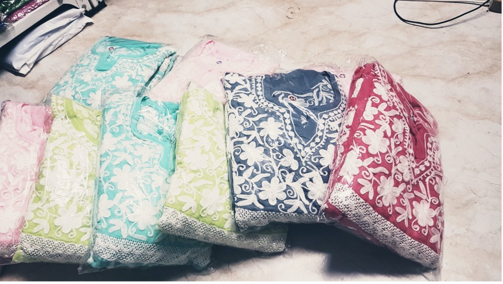 A row of multi-coloured kurtas in the same design. They are folded and wrapped inside transparent plastic packaging. They are lying on a tiled beige floor. Each has heavy white embroidery around the neckline. Each is resting on top of the previous one, sliding off towards the floor. Starting from the left, there is pale pink, lime green, turquoise blue, lime green, navy blue, and bright red one.